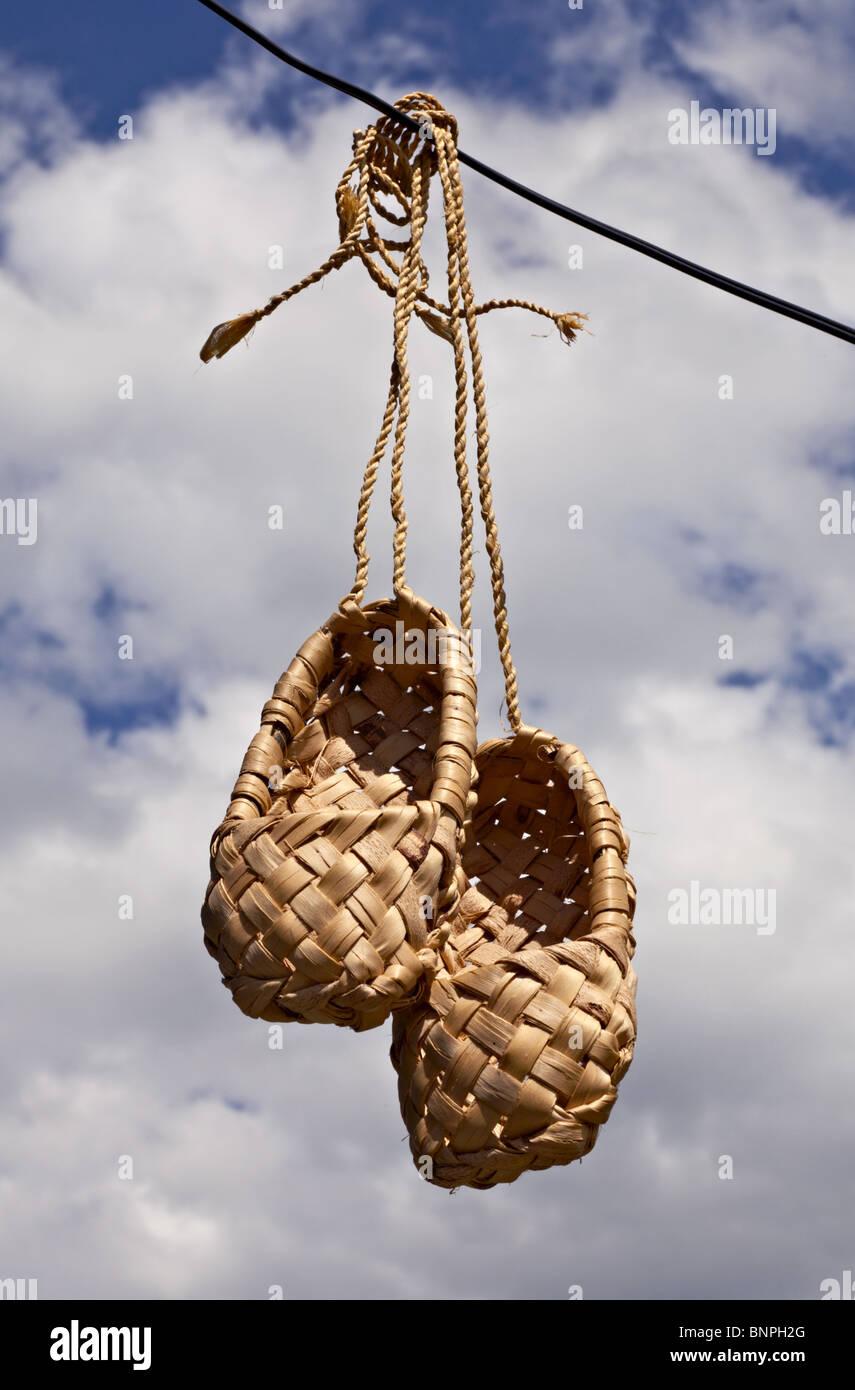 Bast shoes hanging against the sky background - Stock Image