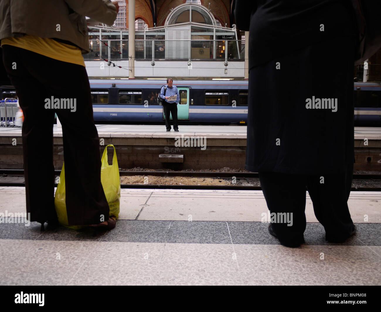 rail passengers waiting on platform at liverpool street station - Stock Image