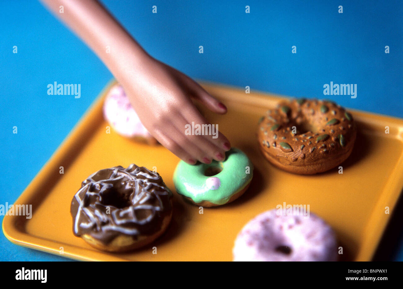 A woman's hand reaching for  a donut. - Stock Image