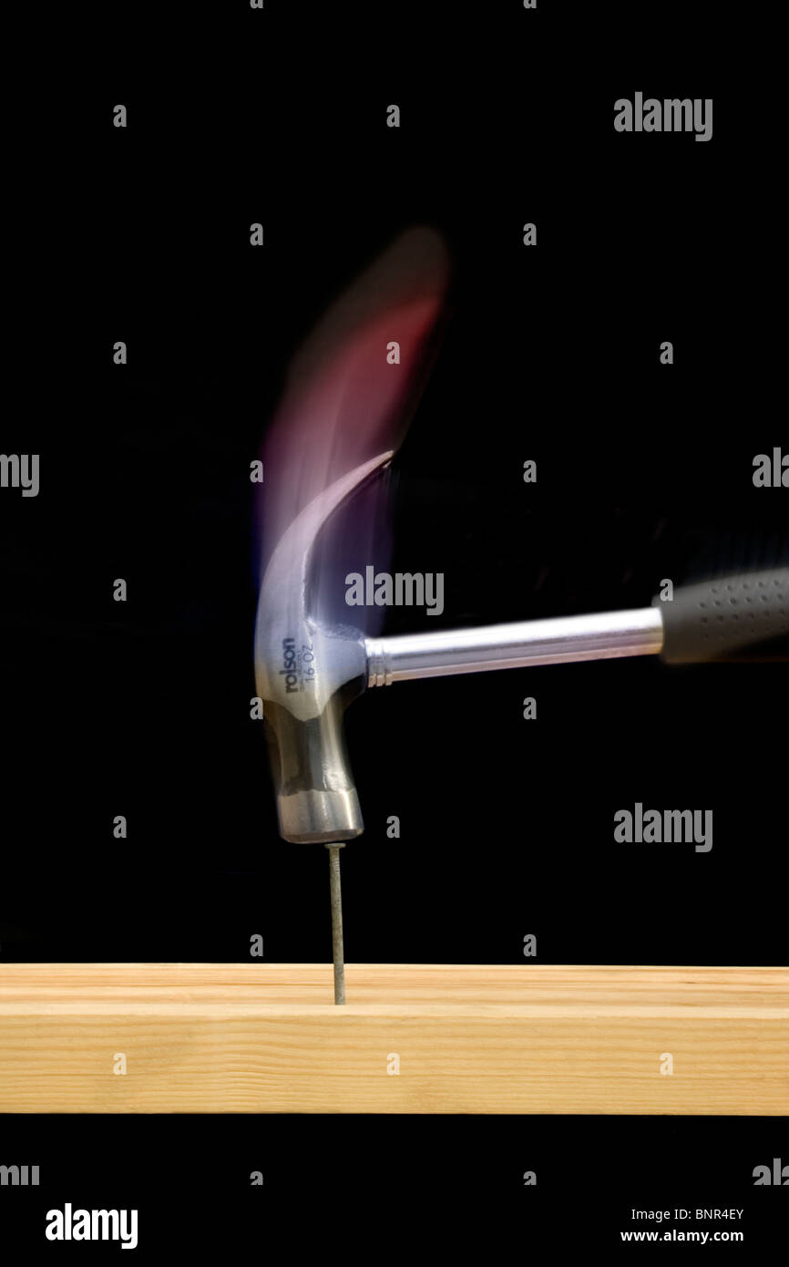 An 'action' shot of a claw hammer hitting a nail on the head, with red to blue trails from the claw colour - Stock Image
