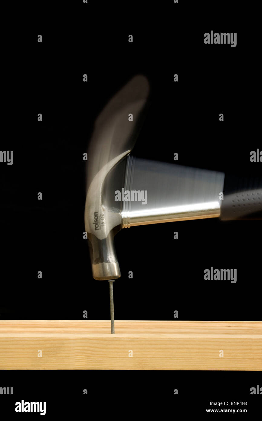 An 'action' shot of a claw hammer hitting a nail on the head - Stock Image