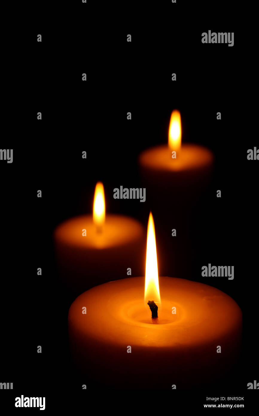 Three burning candles (focus on front candle) - Stock Image