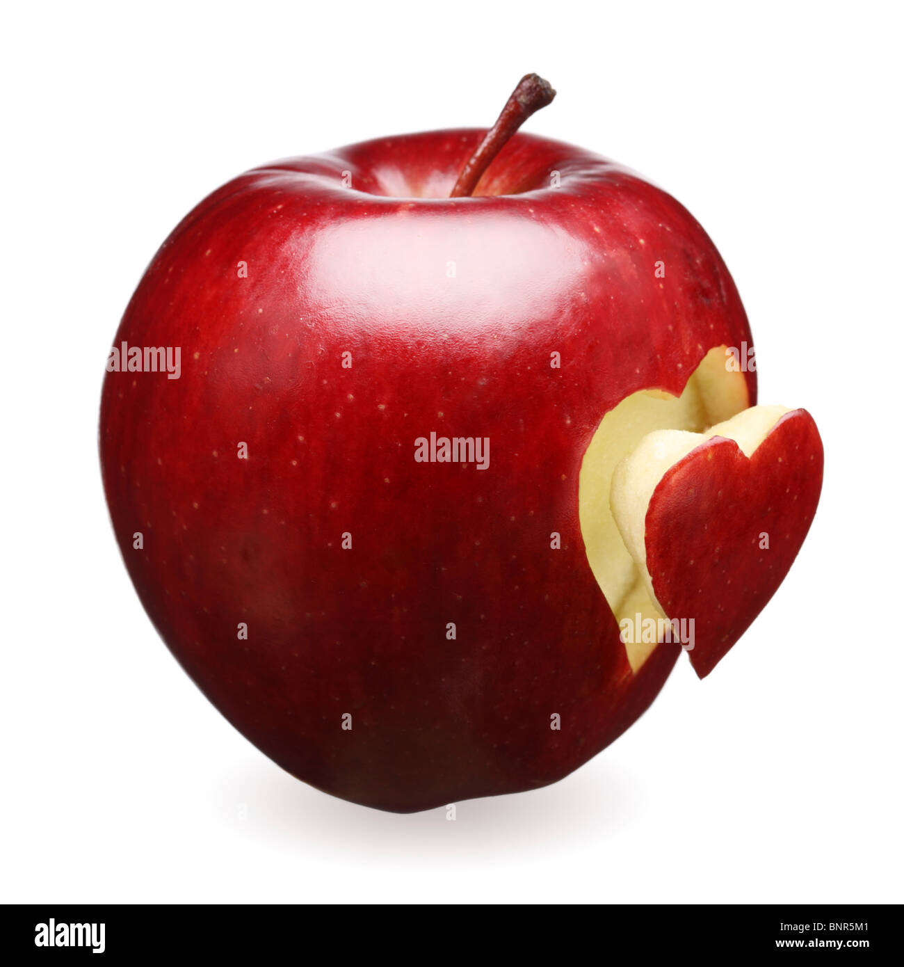 Red apple with a heart shape cut-out (isolated against white) - Stock Image