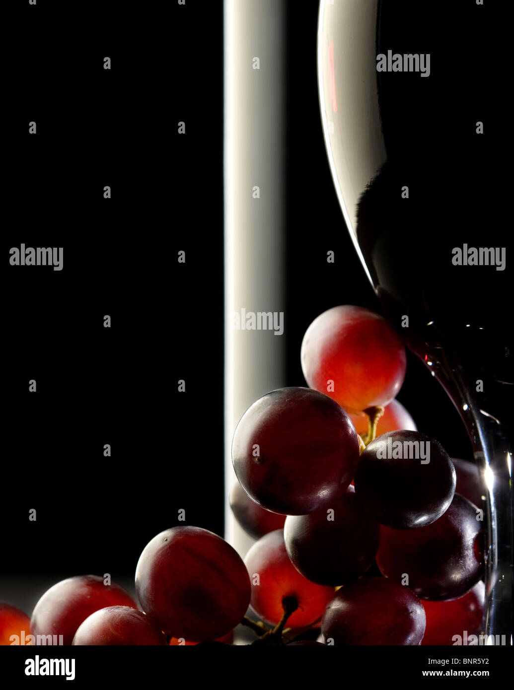 Close-up of red grapes and a glass / bottle of red wine - Stock Image
