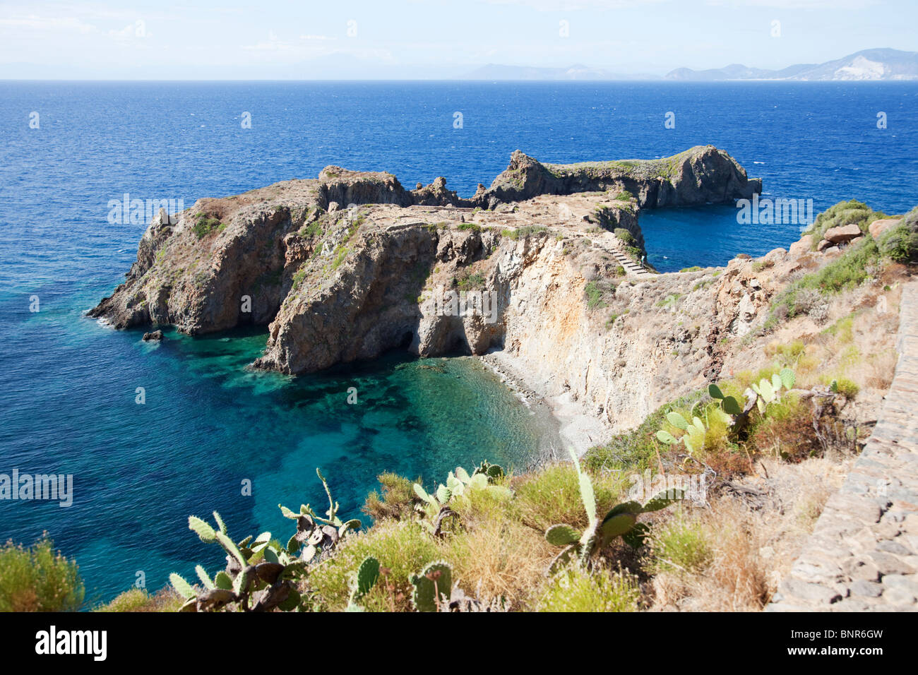 Headland Punta Milazzese of island Panarea of Aeolian Islands contain prehistory ruin site on the top. - Stock Image