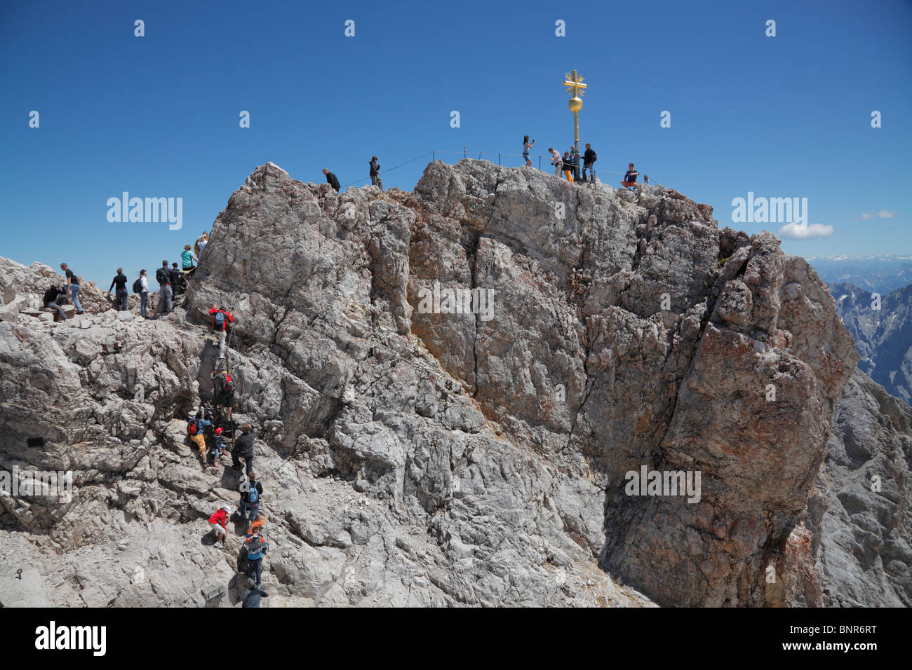 Tourists climbing to the Golden Cross - the highest point in Germany on the summit of Zugspitze at 2,962m above Stock Photo