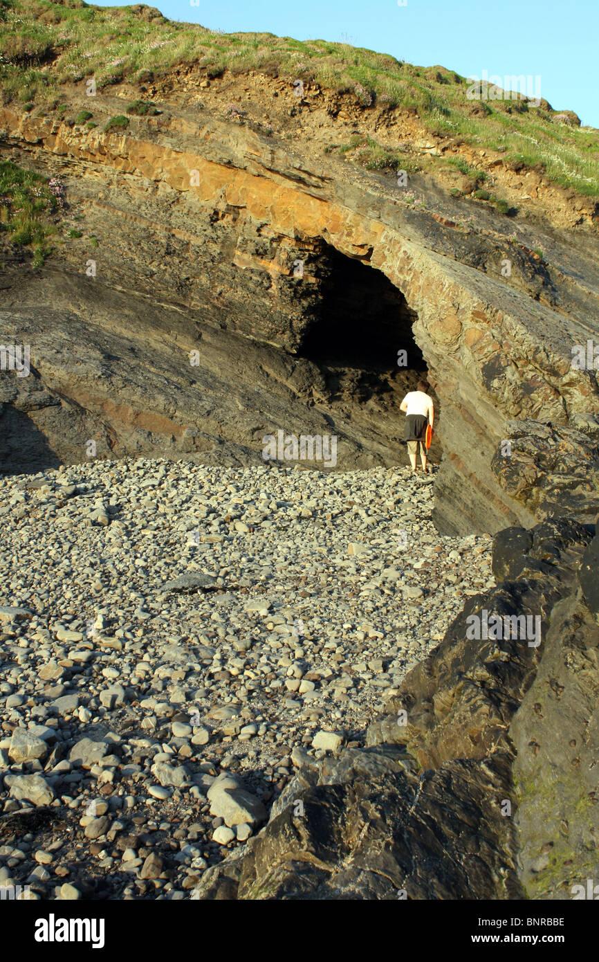 Man exploring cave at Broadhaven Pembrokeshire - Stock Image