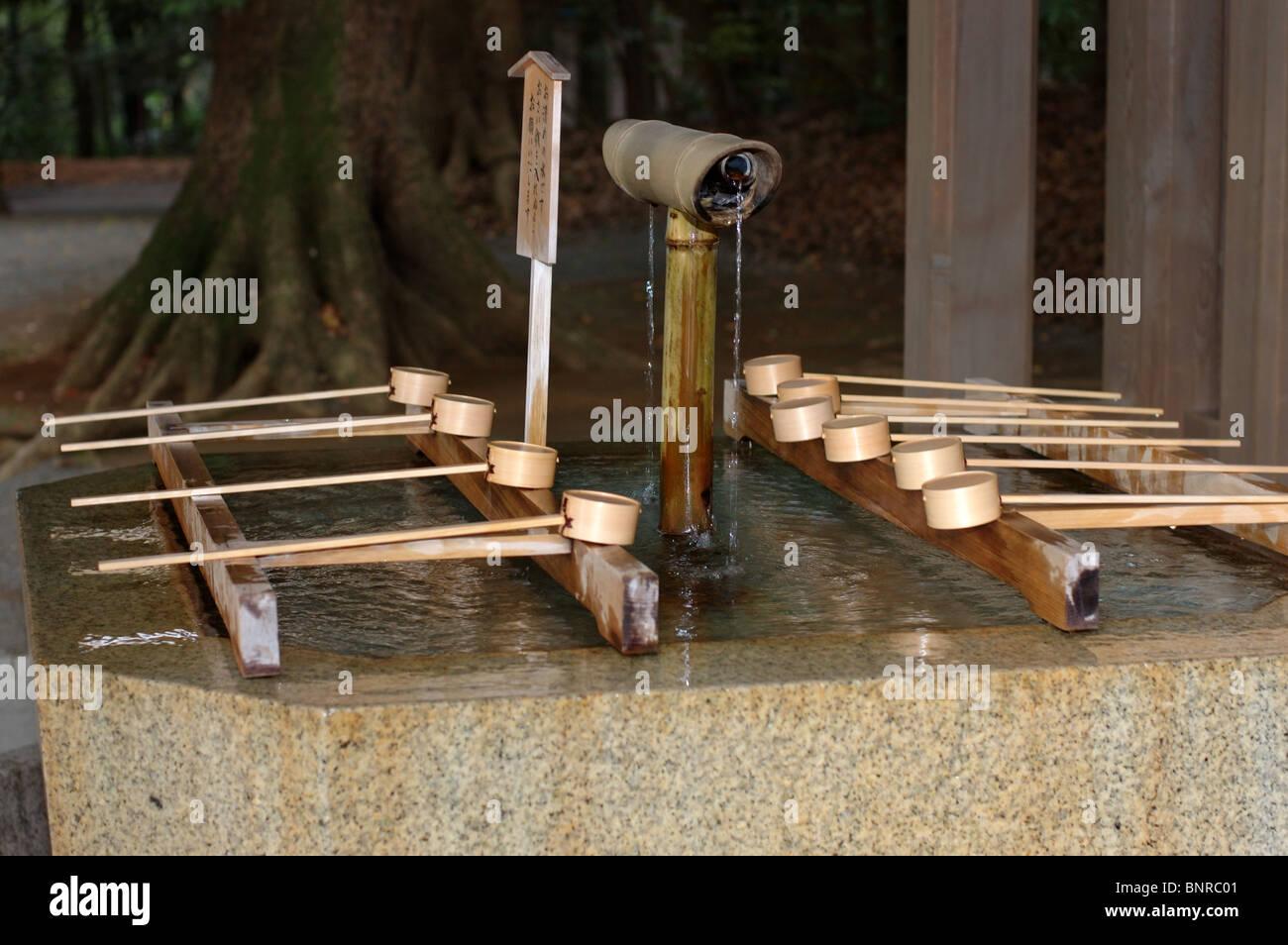 Use a bamboo ladle hishaku to cleanse your body and mind before entering Meiji Jingu, a Shinto shrine. Tokyo, Japan. - Stock Image
