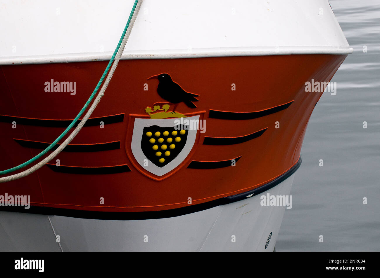 The Cornish coat of arms and the bow of a fishing boat moored in Newlyn hrabour in Cornwall. - Stock Image