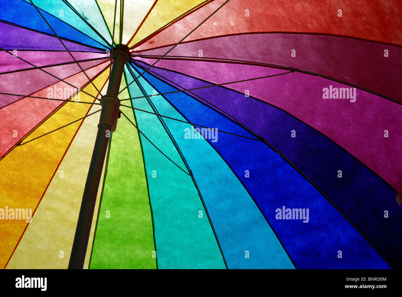 Rainbow colored sun umbrella at the beach against clear blue sky. - Stock Image