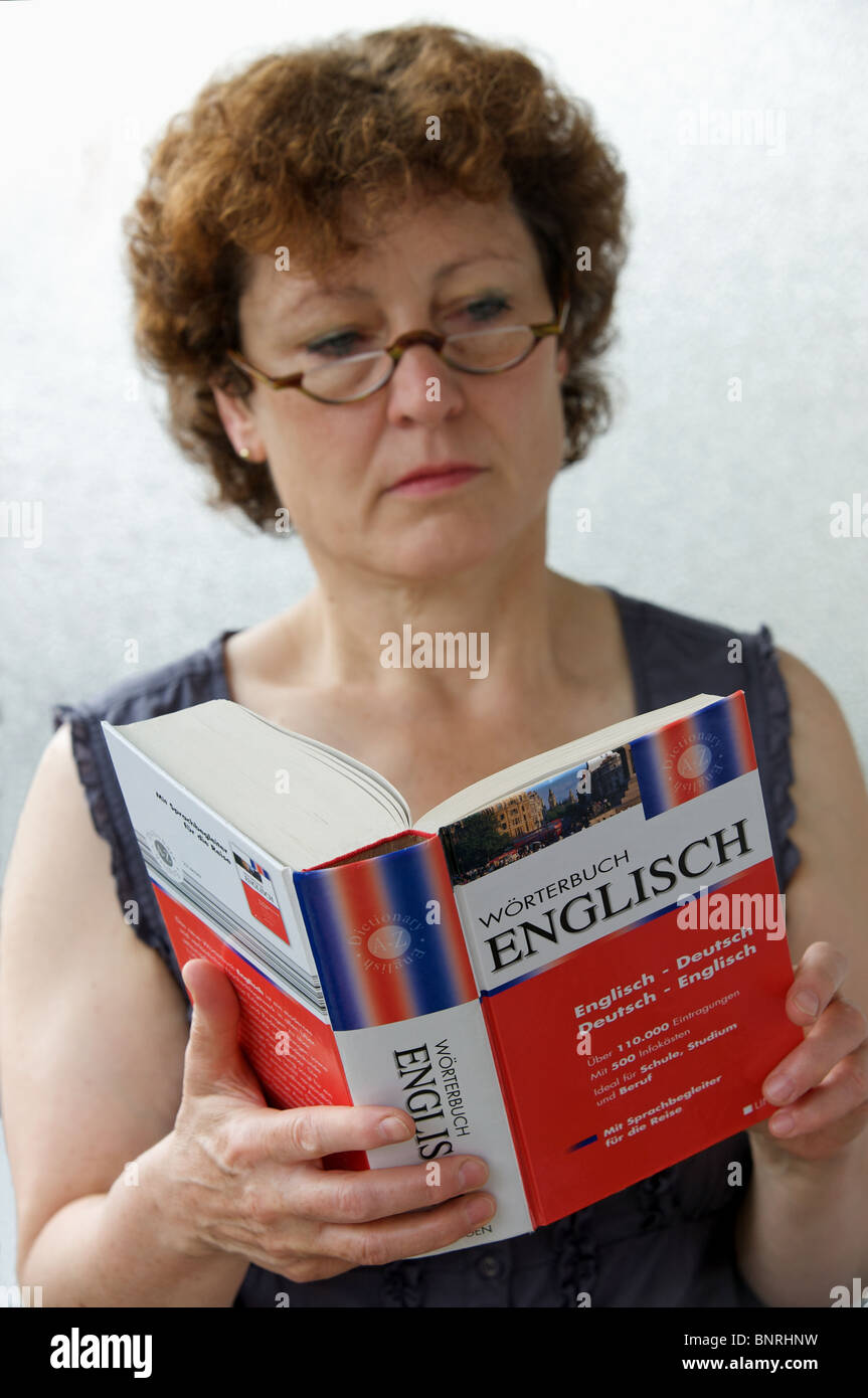Woman looking at German to English dictionary published by Worterbuch - Stock Image