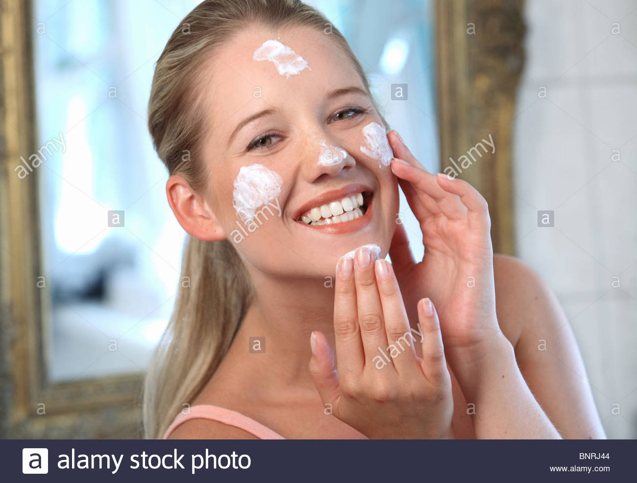 woman creaming face - Stock Image