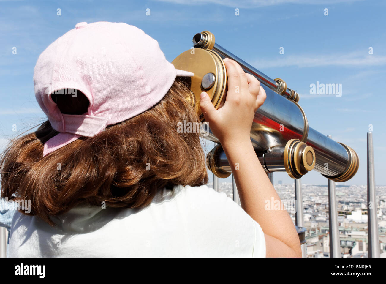 A young girl watching on a spy-glass - Stock Image