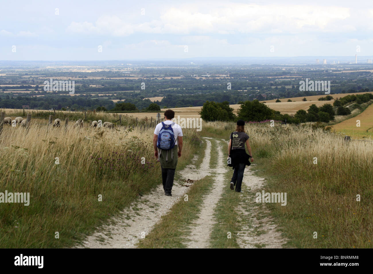 Two people walking along the White Horse hill circular route in Oxfordshire, England - Stock Image