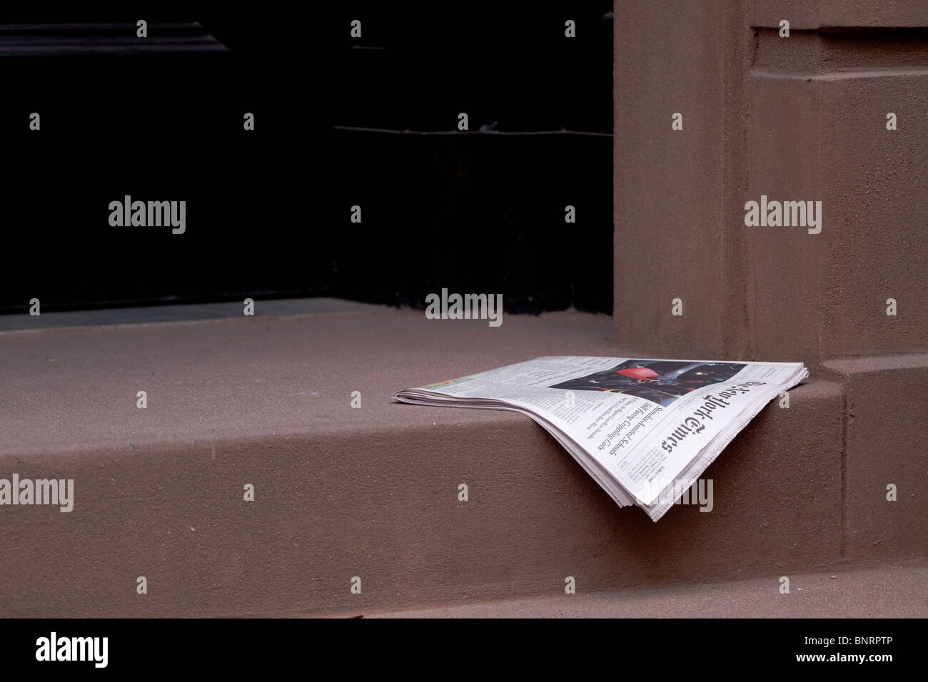 a newspaper delivered and lying on a doorstep outside a city house in Greenwich Village, Manhattan, New York, USA - Stock Image