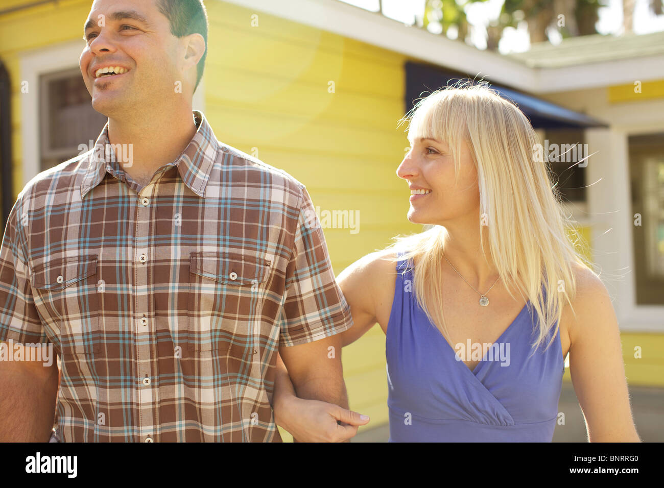 Female puts her arm around male's arm and couple walk together. - Stock Image