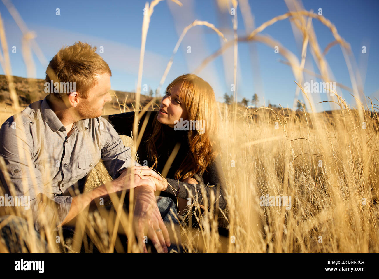 Couple sitting on the ground of an open field look at each other and smile. - Stock Image