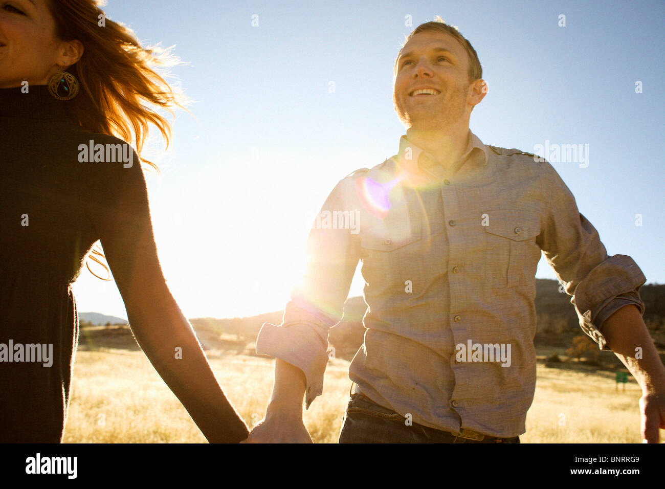 Couple run while holding hands and smiling in an open field. Stock Photo