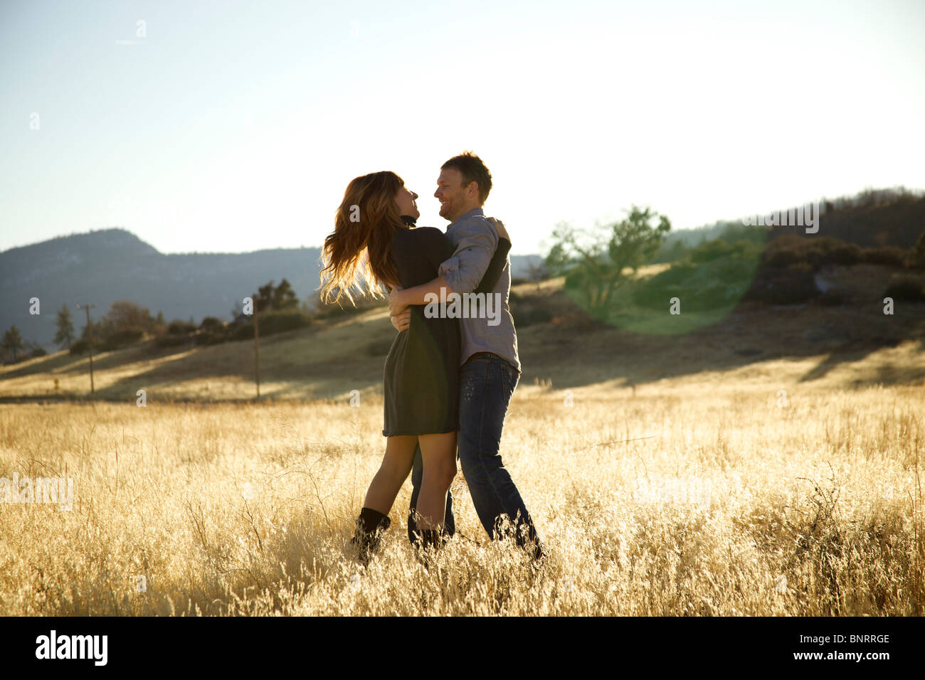 Happy couple hugging in an open field. - Stock Image