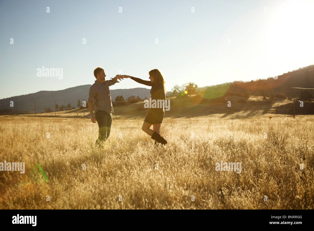 Happy couple dancing in an open field. - Stock Image