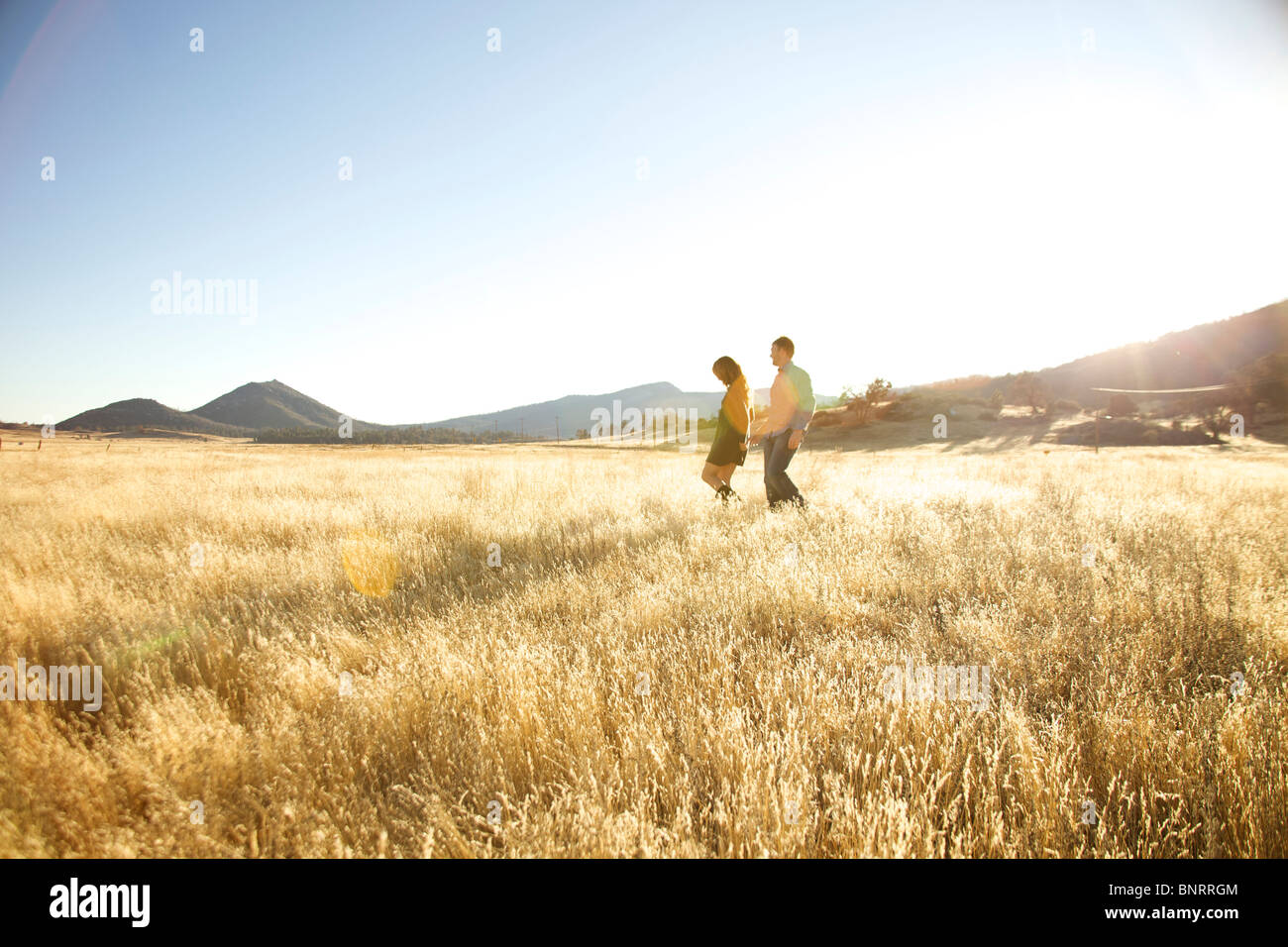 db7d6fa9a0fed7 Couple in the far distance walking together in an open field. - Stock Image
