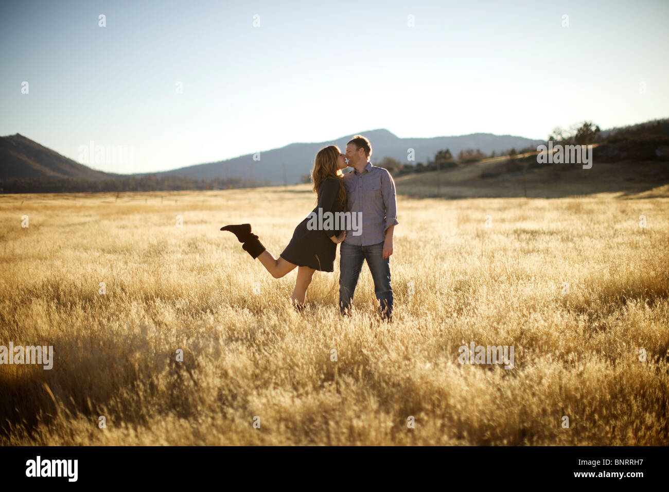 Female approaches male for a kiss in an open field. Stock Photo