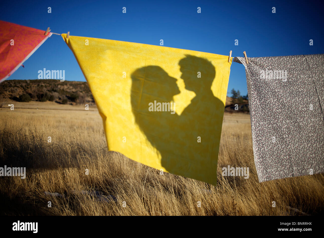 A couple's shadow on a yellow fabric hung on a clothes line in an open field. - Stock Image