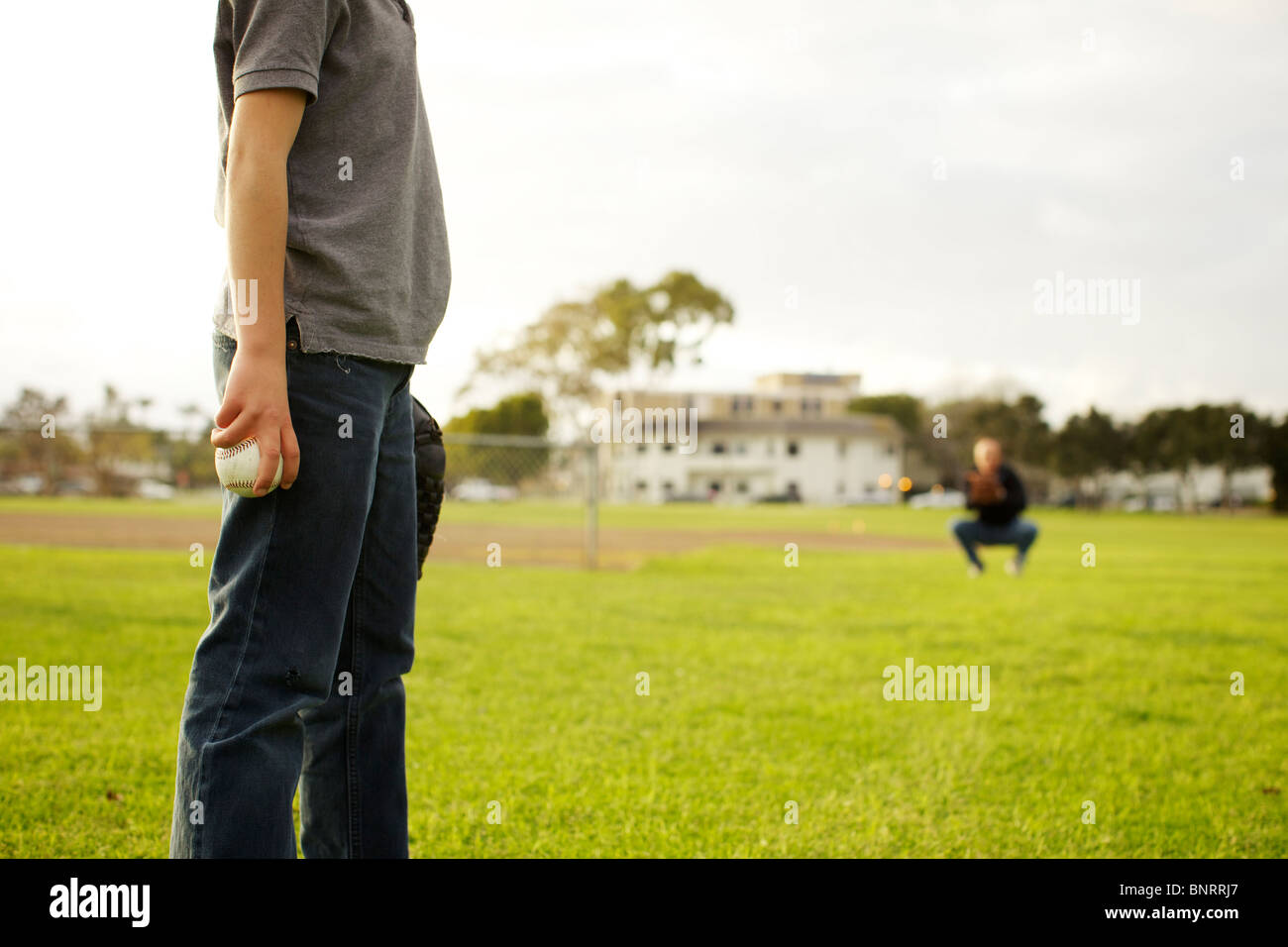 Boy gets ready to throw a baseball for his dad to catch at the park. - Stock Image
