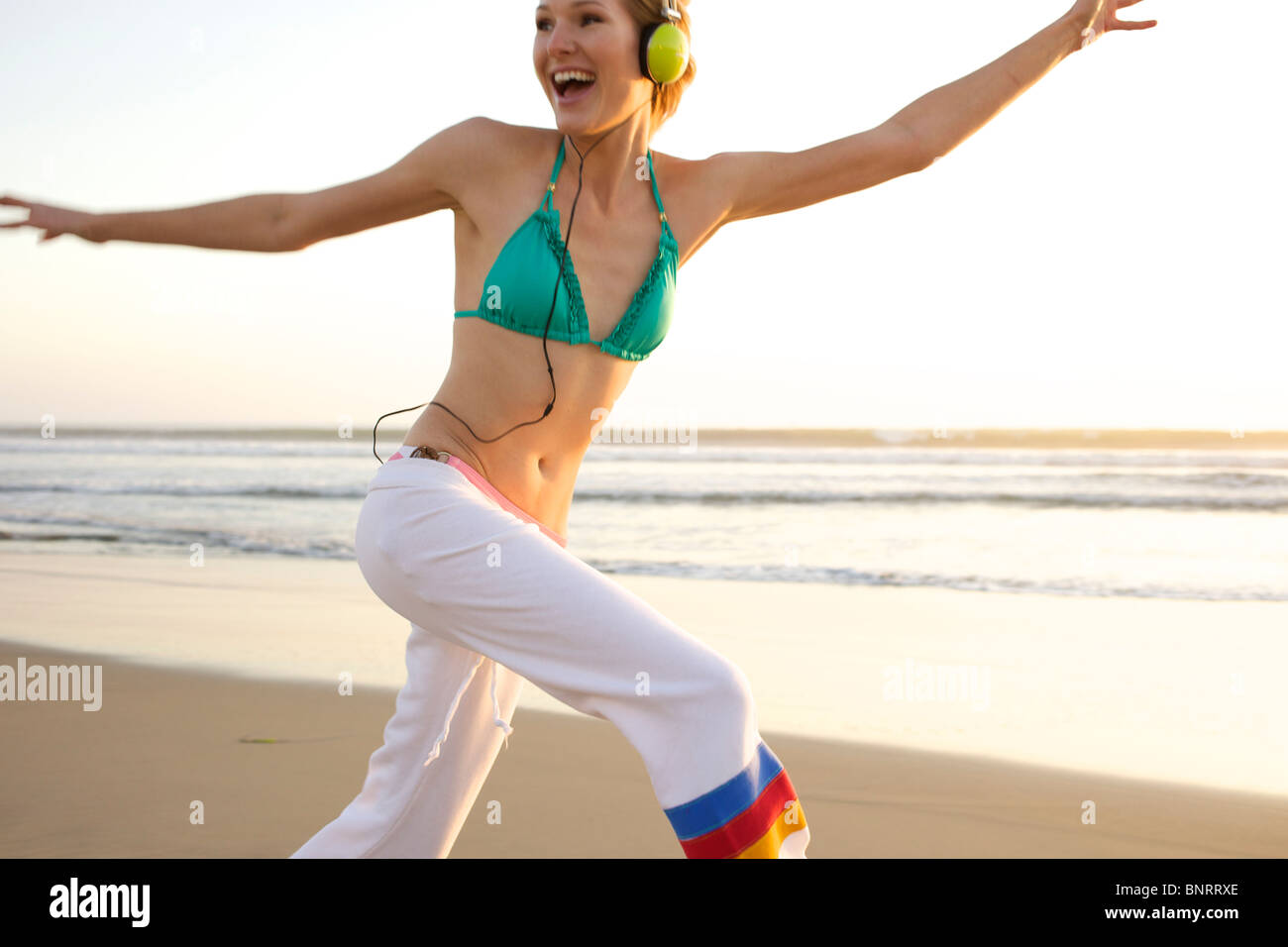 Young female wearing a headset jumps and smiles at the beach. - Stock Image