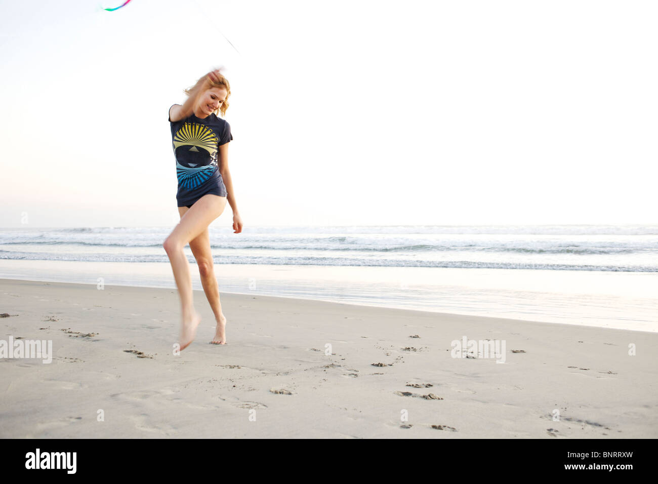 Young female plays with a colorful ribbon at the beach. - Stock Image