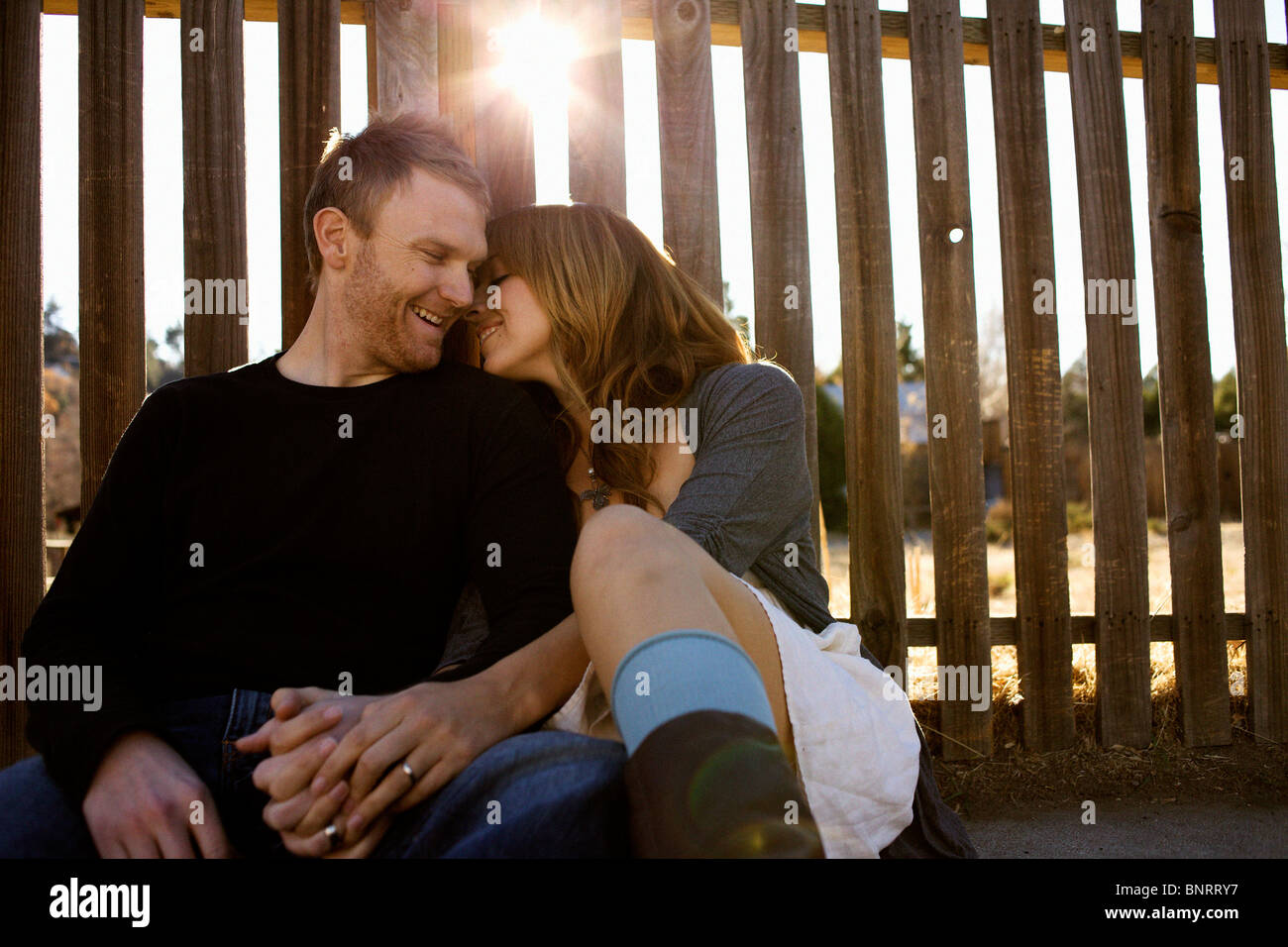 Couple sits against a fence. - Stock Image
