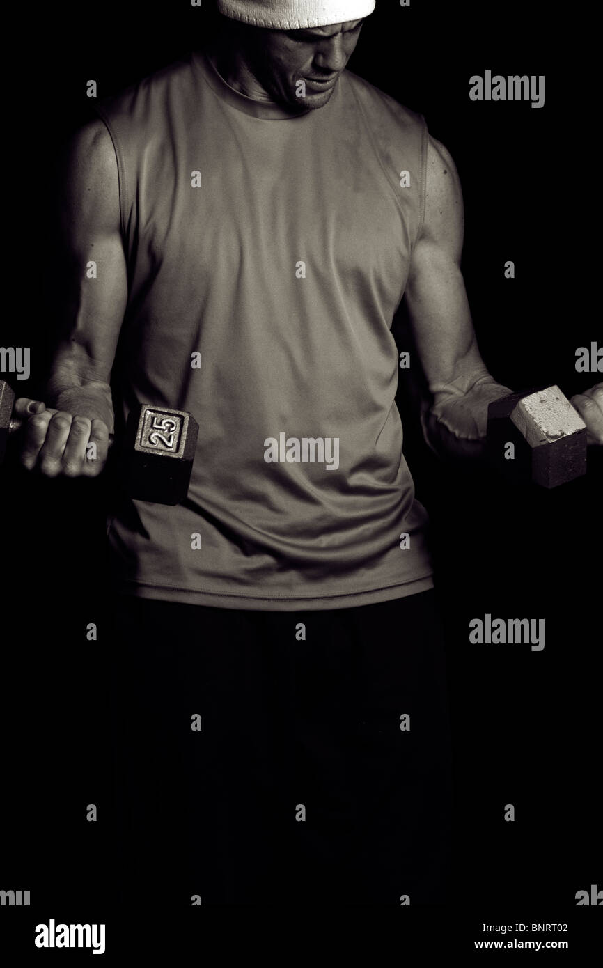 A young man lifts weights. - Stock Image