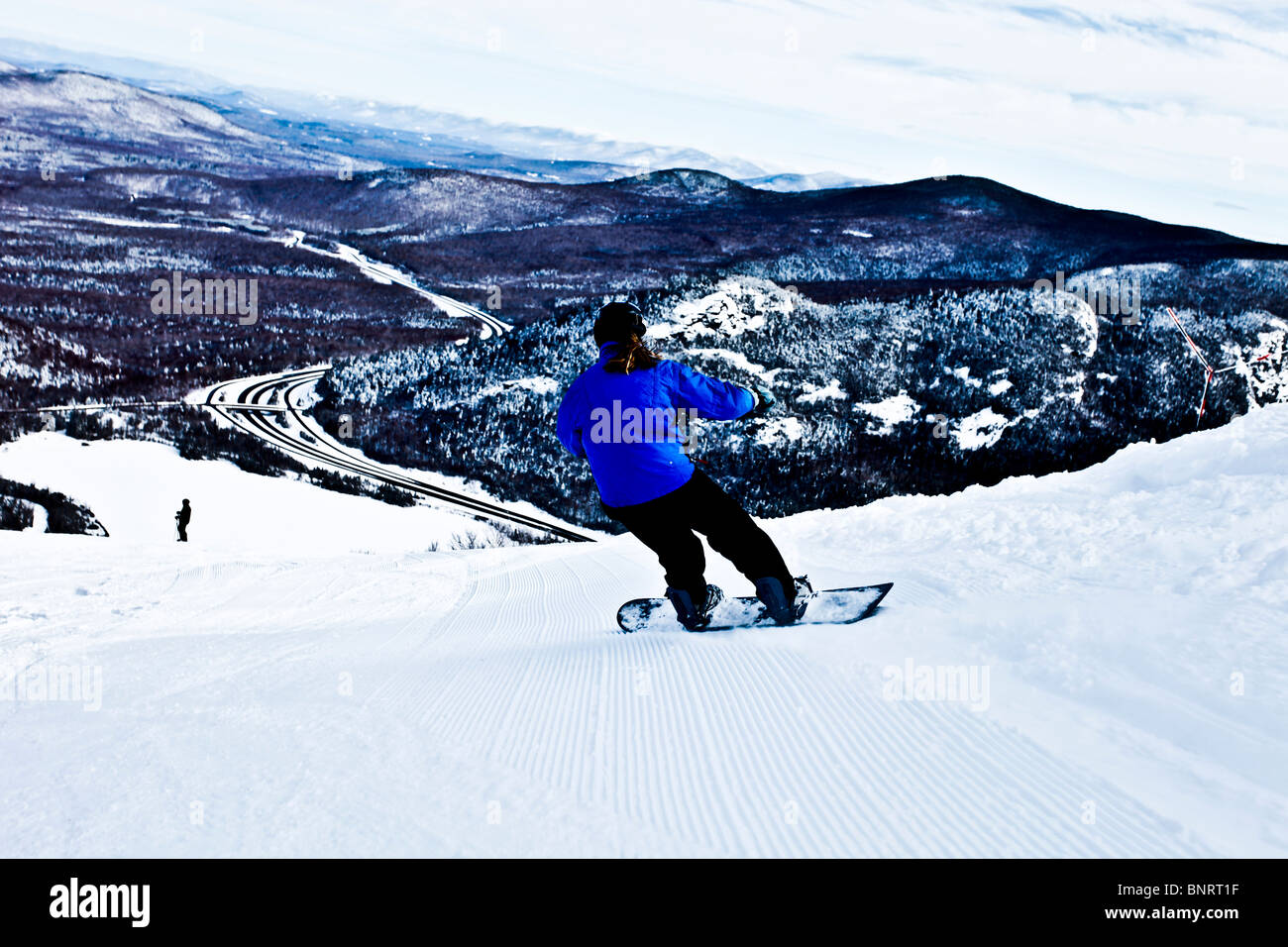 A female snowboarder carves in freshly groomed corduroy in New Hampshire. - Stock Image