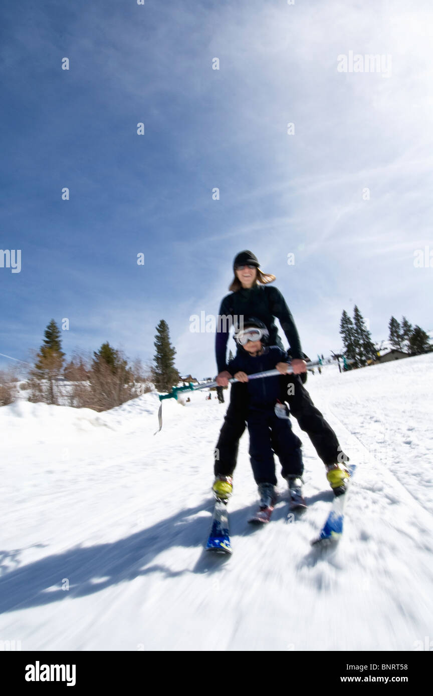 A young woman patiently teaches her nephew how to ski in Truckee, California. - Stock Image