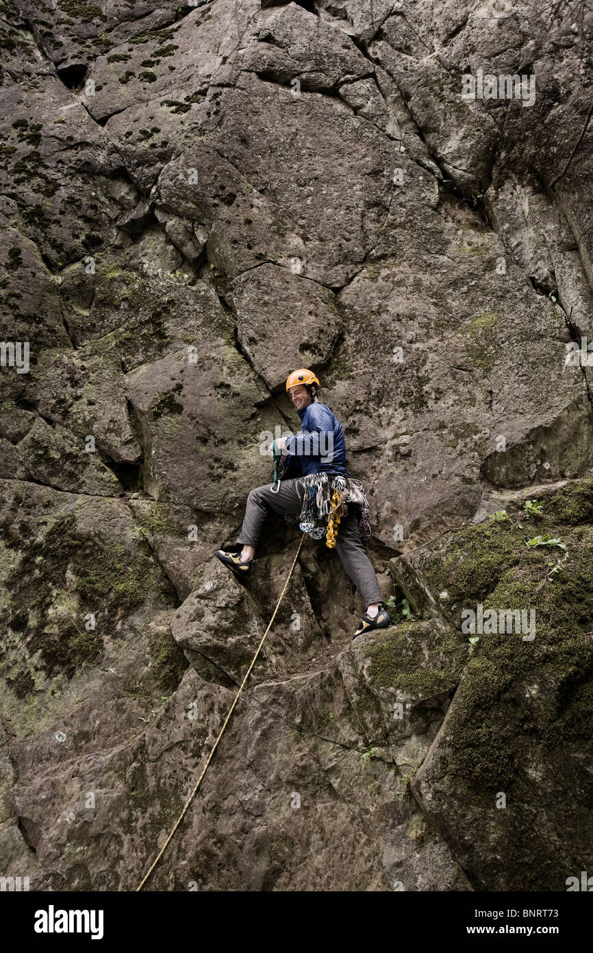 A lead climber pauses while climbing. - Stock Image
