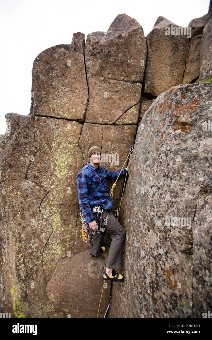 A climber pauses near the top of a rock route. - Stock Image