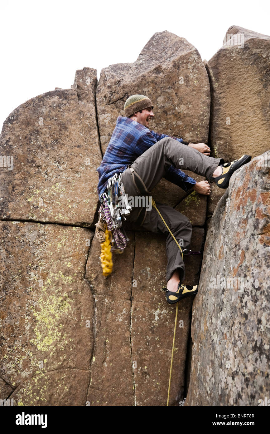 A lead climber reaches the top. - Stock Image