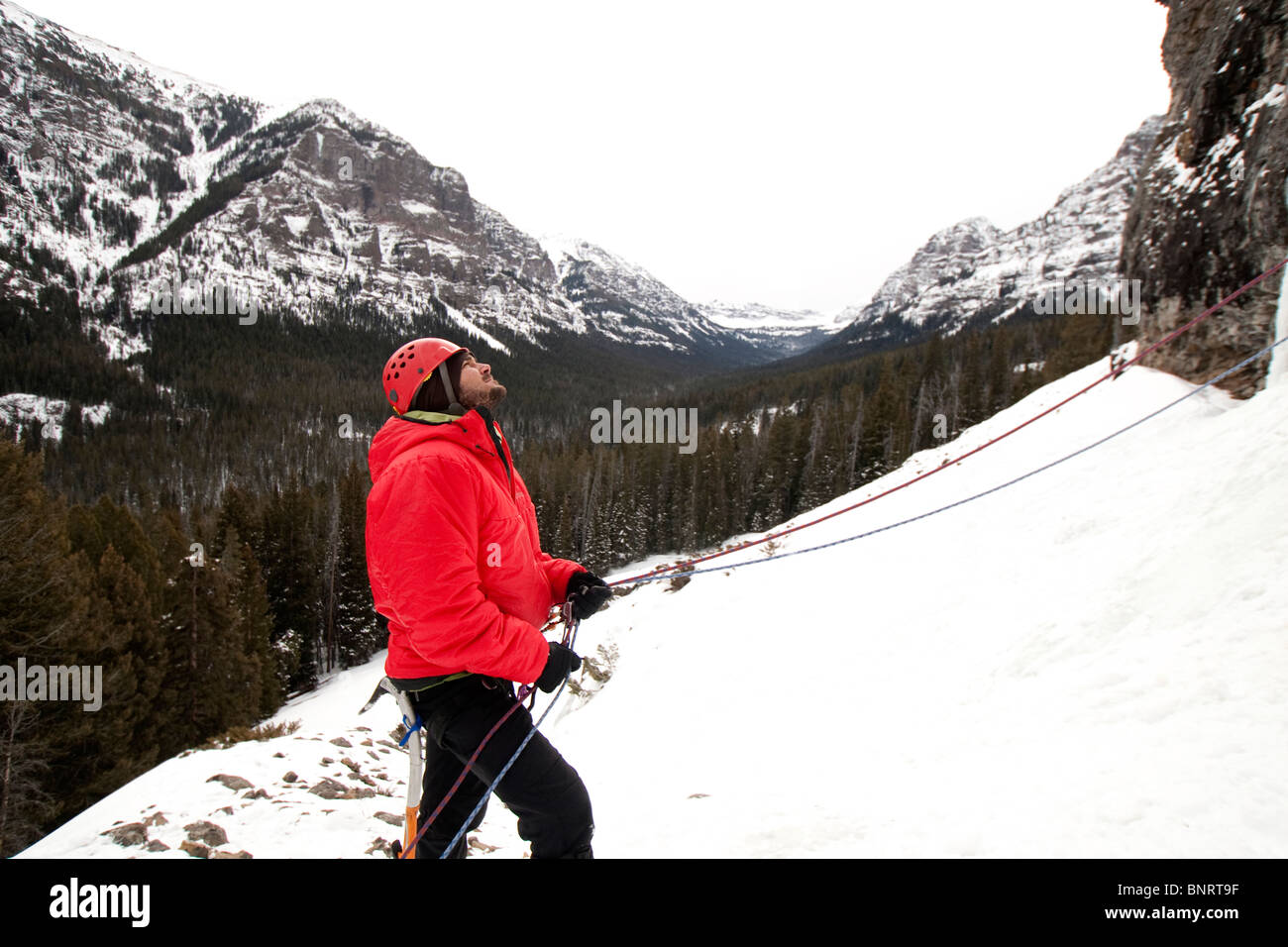 A man belaying an ice climber. - Stock Image