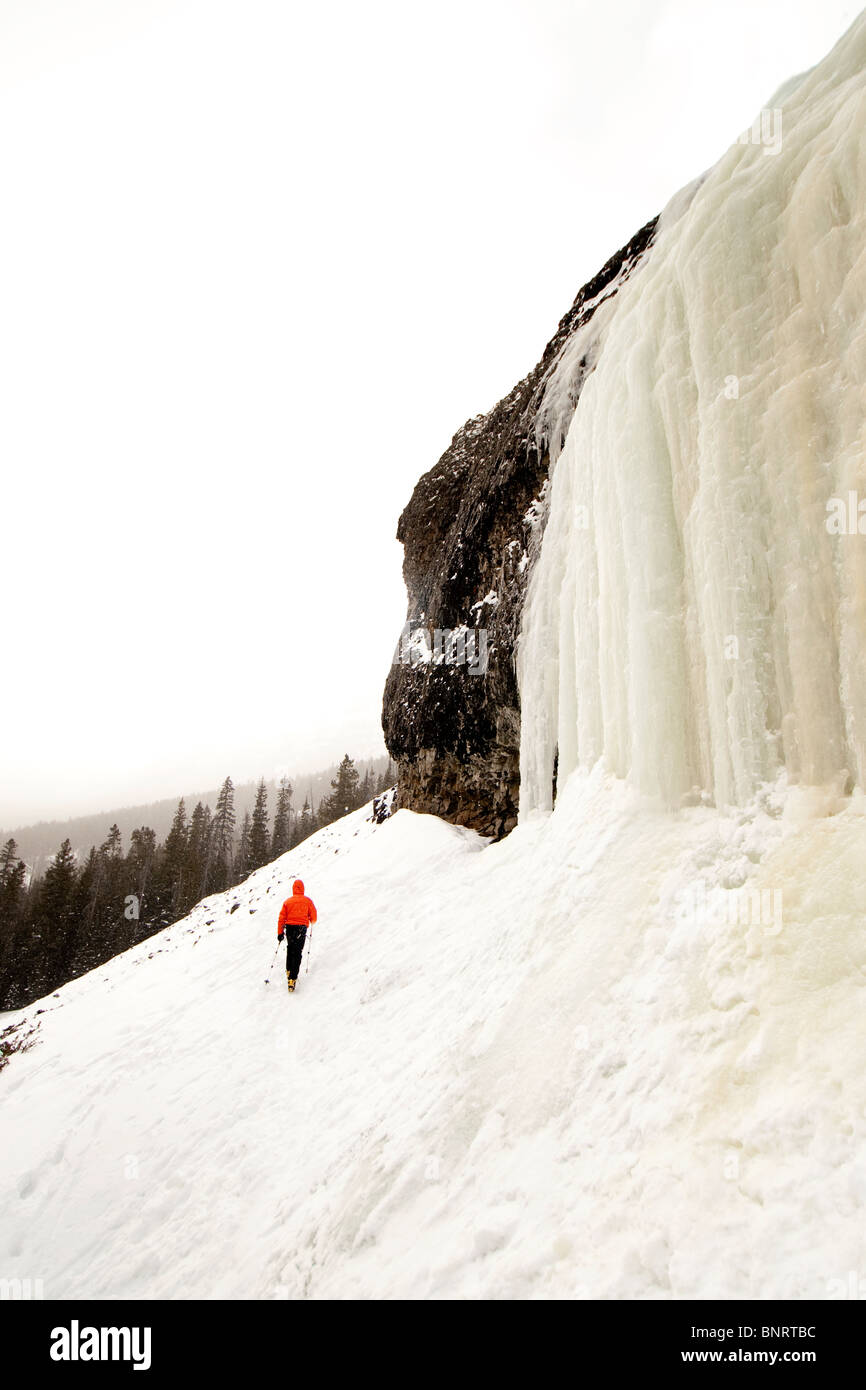 Man hiking in the snow near a frozen waterfall. Stock Photo