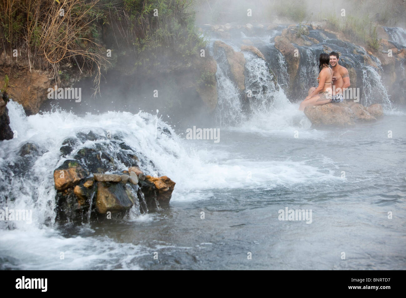 A married couple enjoys natural hot springs in Montana. - Stock Image