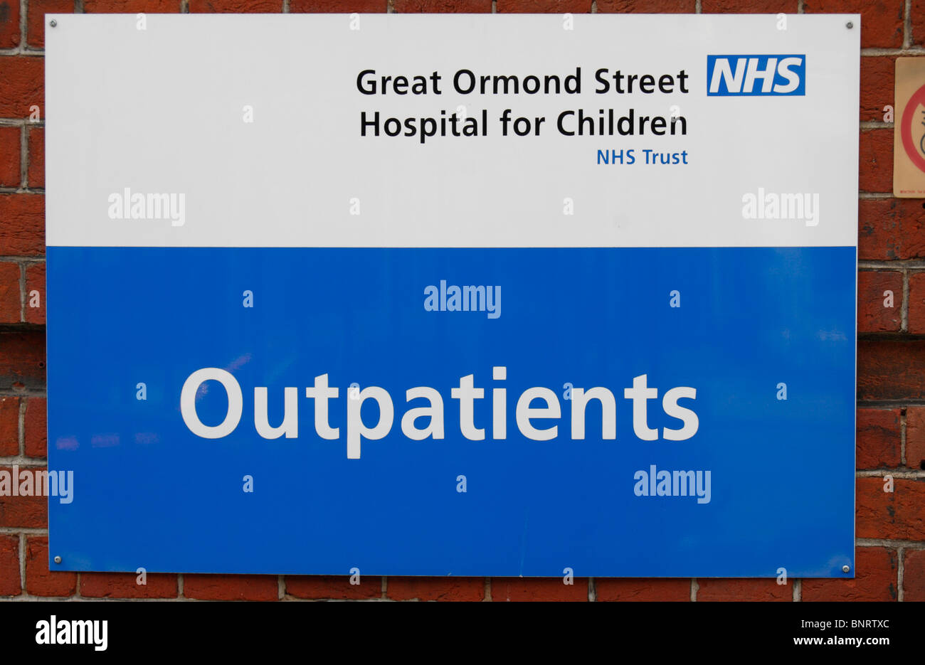 Outpatients sign at the entrance to Great Ormond Street Hospital for Children in London, UK. - Stock Image