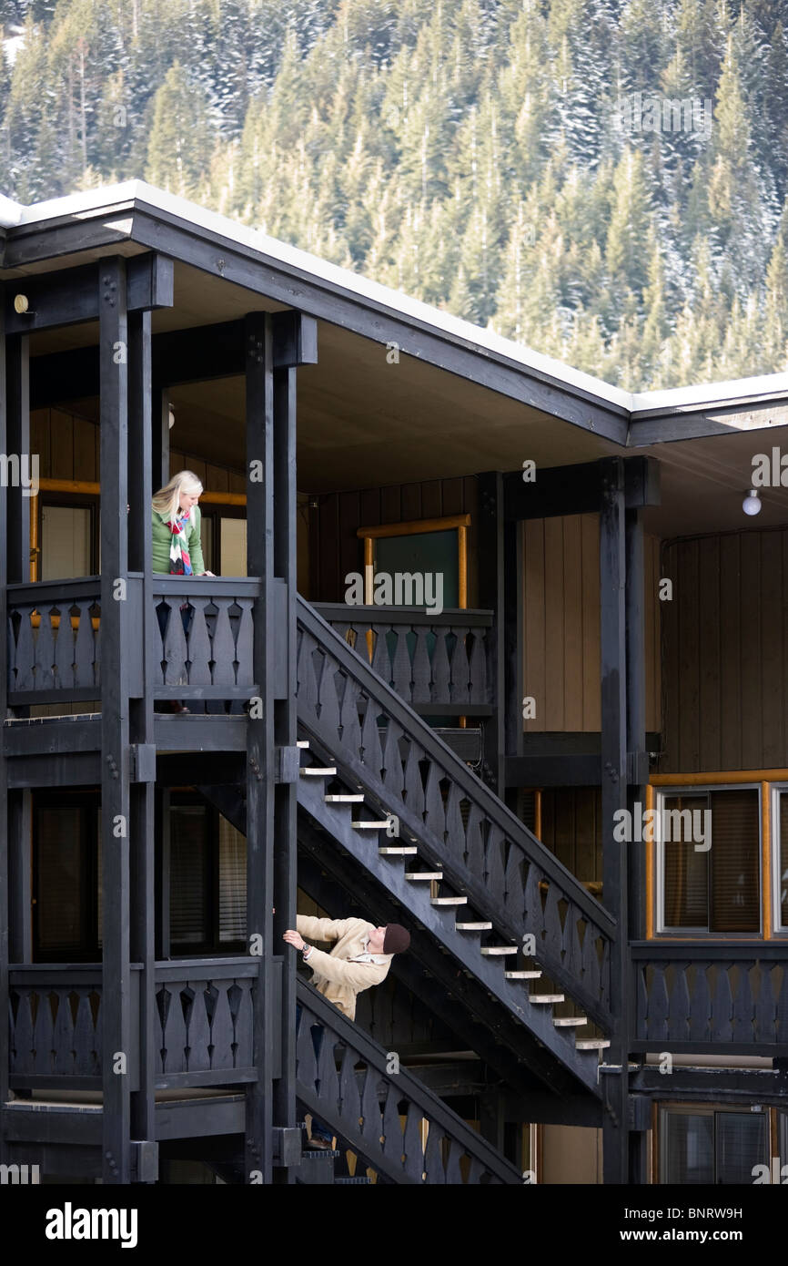 A man and woman communicate from different floors at a mountain lodge. - Stock Image