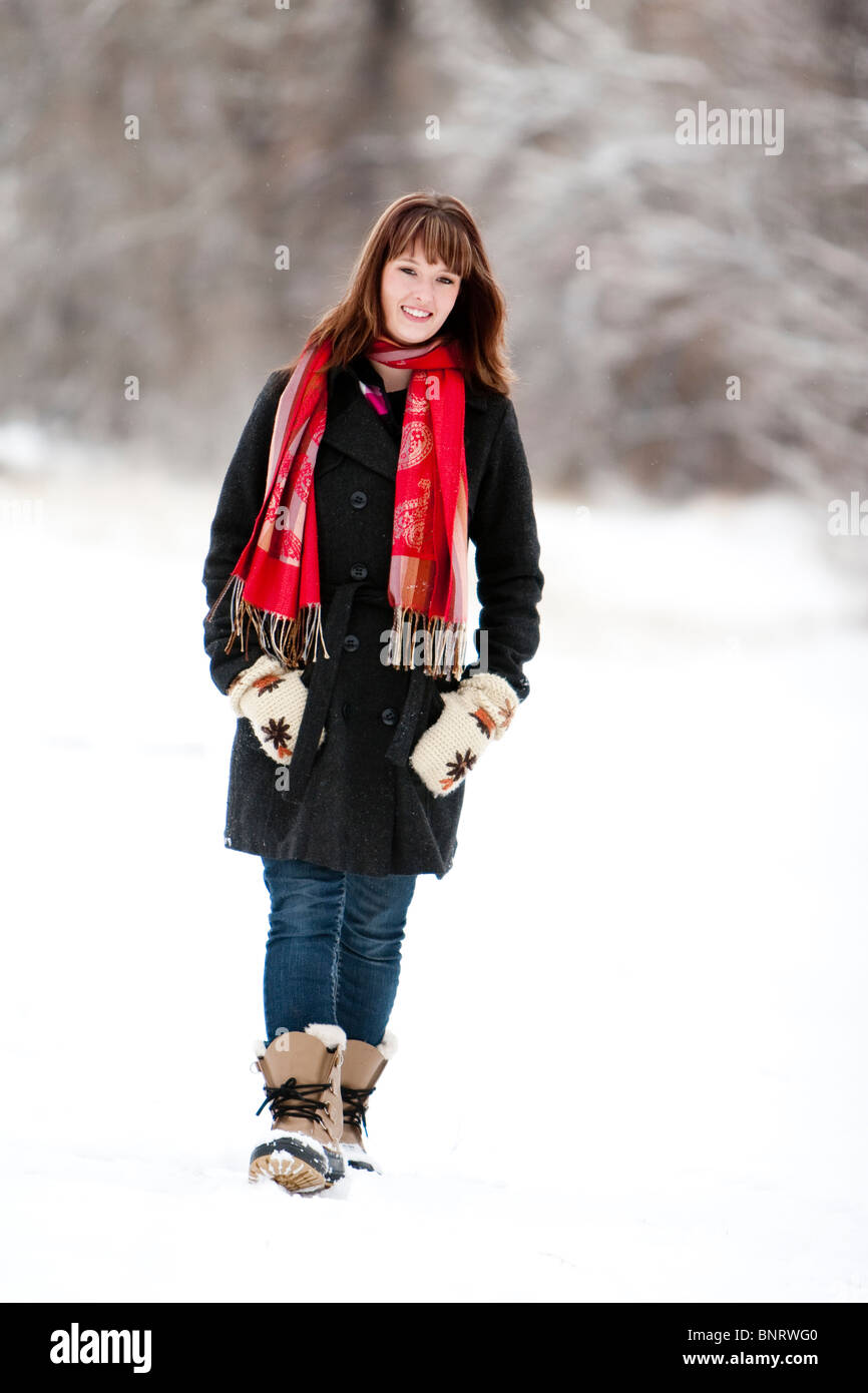 A woman wearing a red scarf walks through a snowy field on an overcast winter day, in Fort Collins, Colorado. - Stock Image