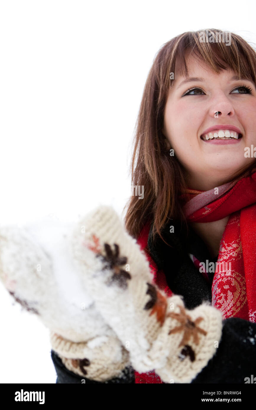 A woman wears a red scarf and packs a snowball with big fuzzy knitted mittens on an overcast winter day, in Fort - Stock Image