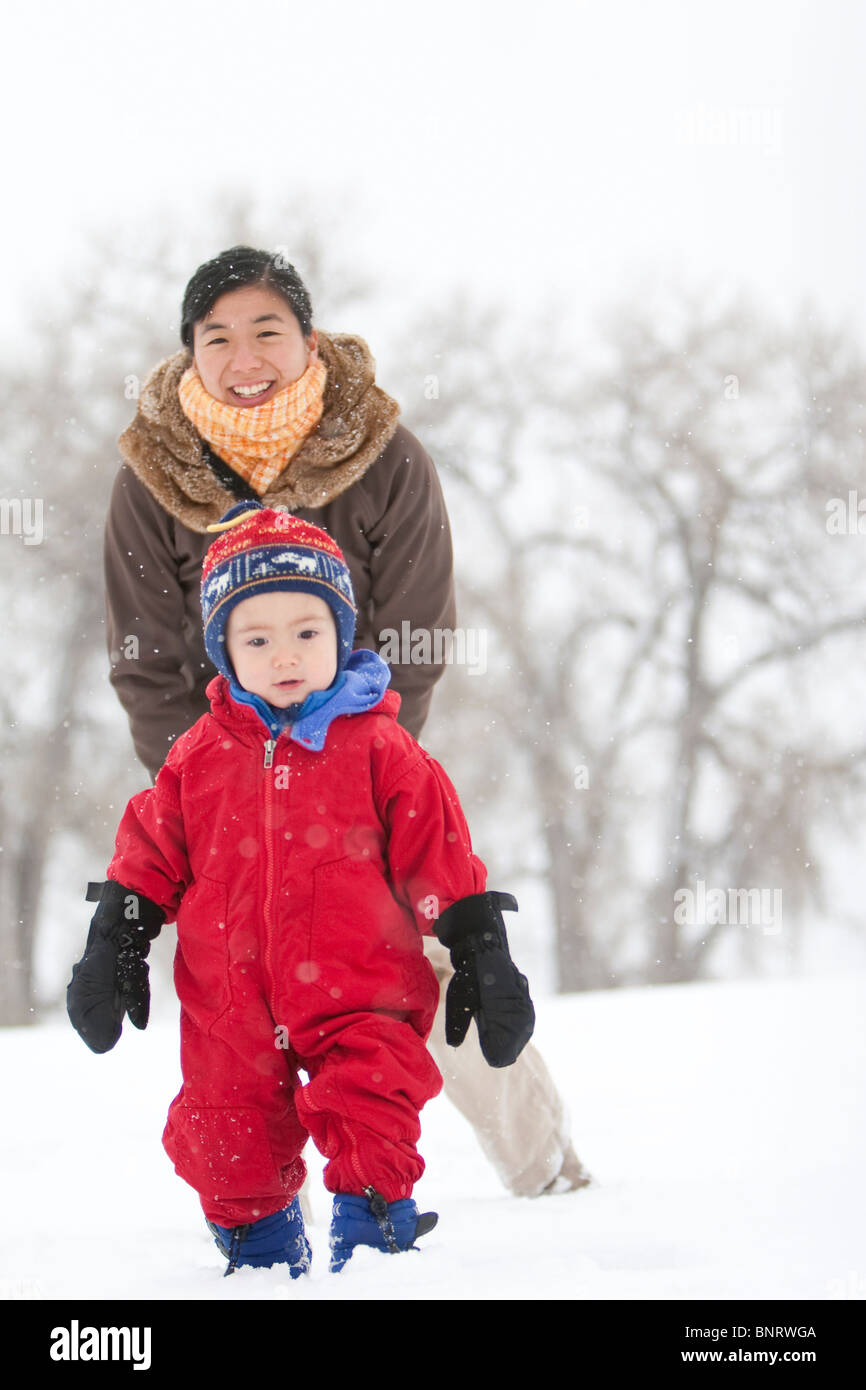 A two year old boy plays in a snowy field during a snowstorm in a red snowsuit with his mother in a park, Fort Collins, - Stock Image