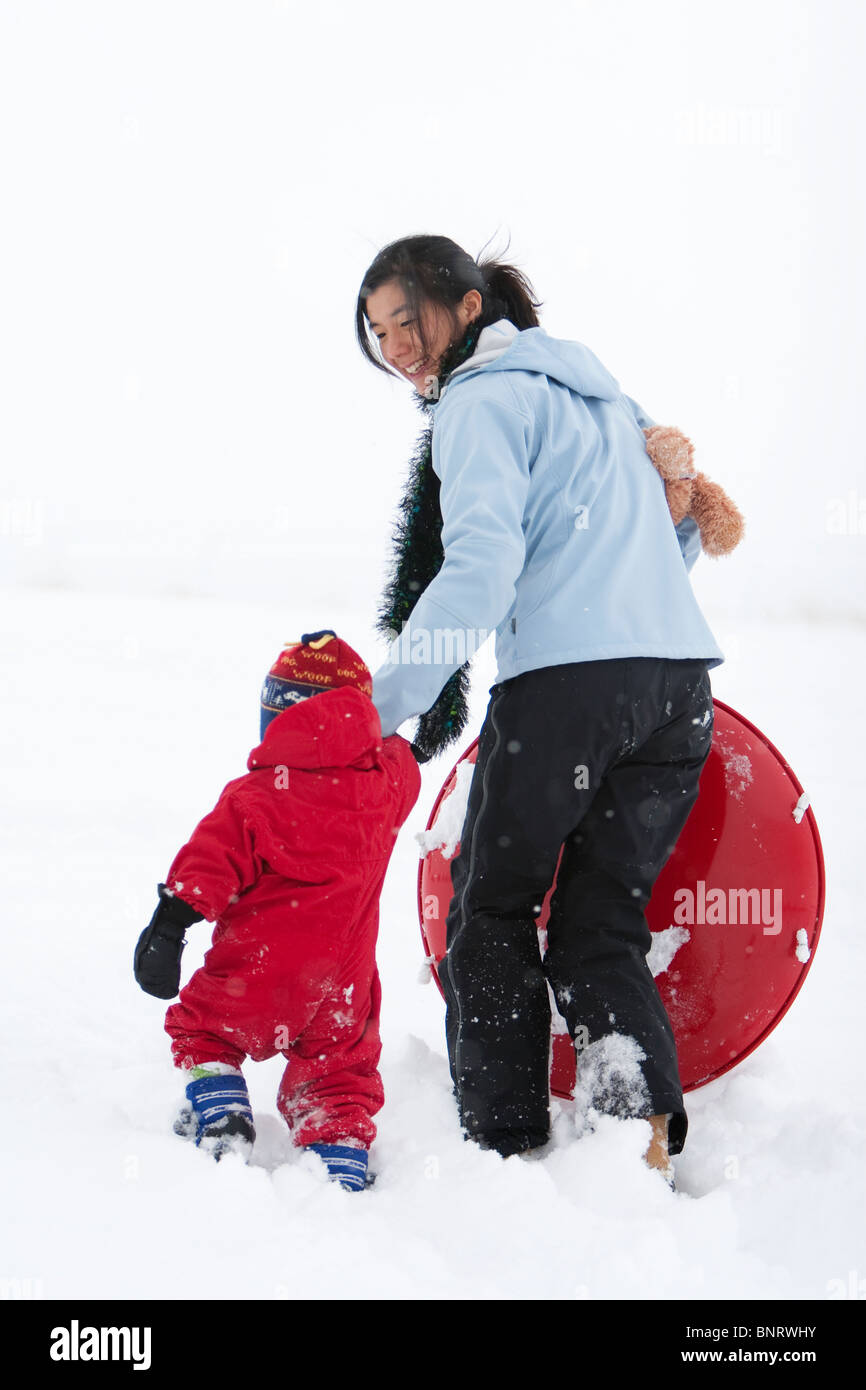 A two year old boy walks through the snow while holding his mother's hand during a day of sledding at the local - Stock Image