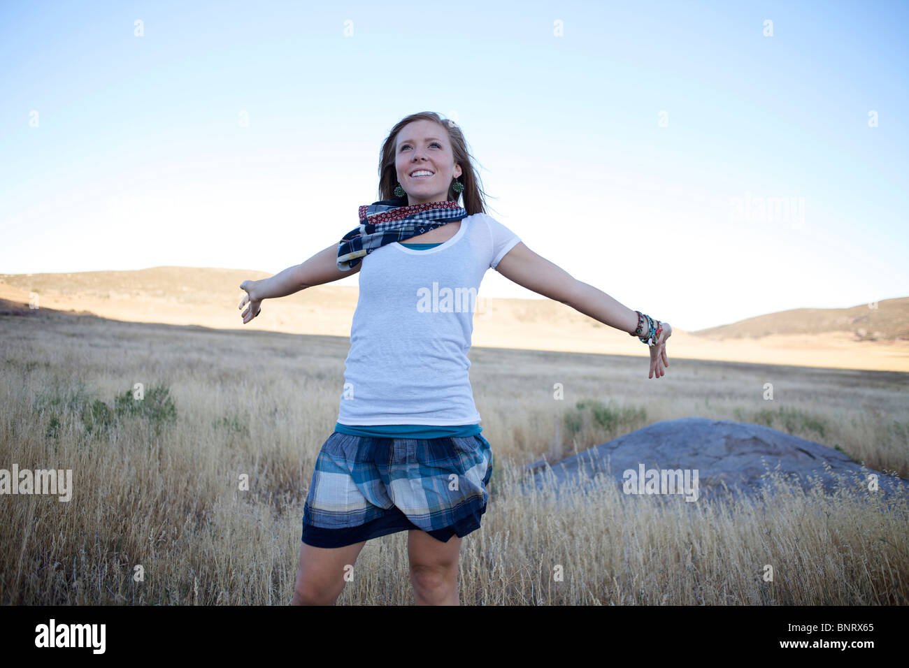 Young lady in an open field opens her arms to feel the wind. - Stock Image