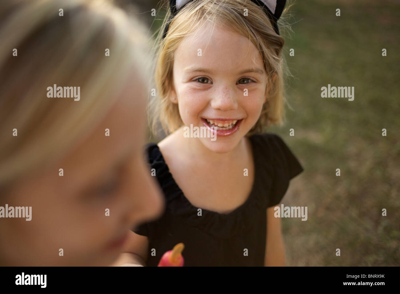 Girl holding her cold treat, wearing cat ears, looks at the camera and smiles. - Stock Image