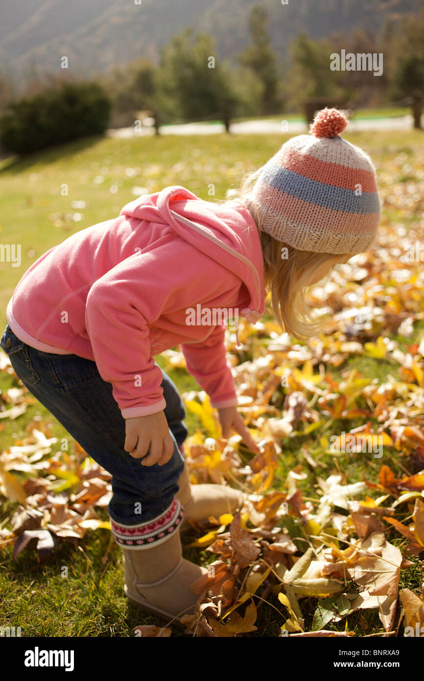 Young girl picks up dry leaves from the ground. - Stock Image