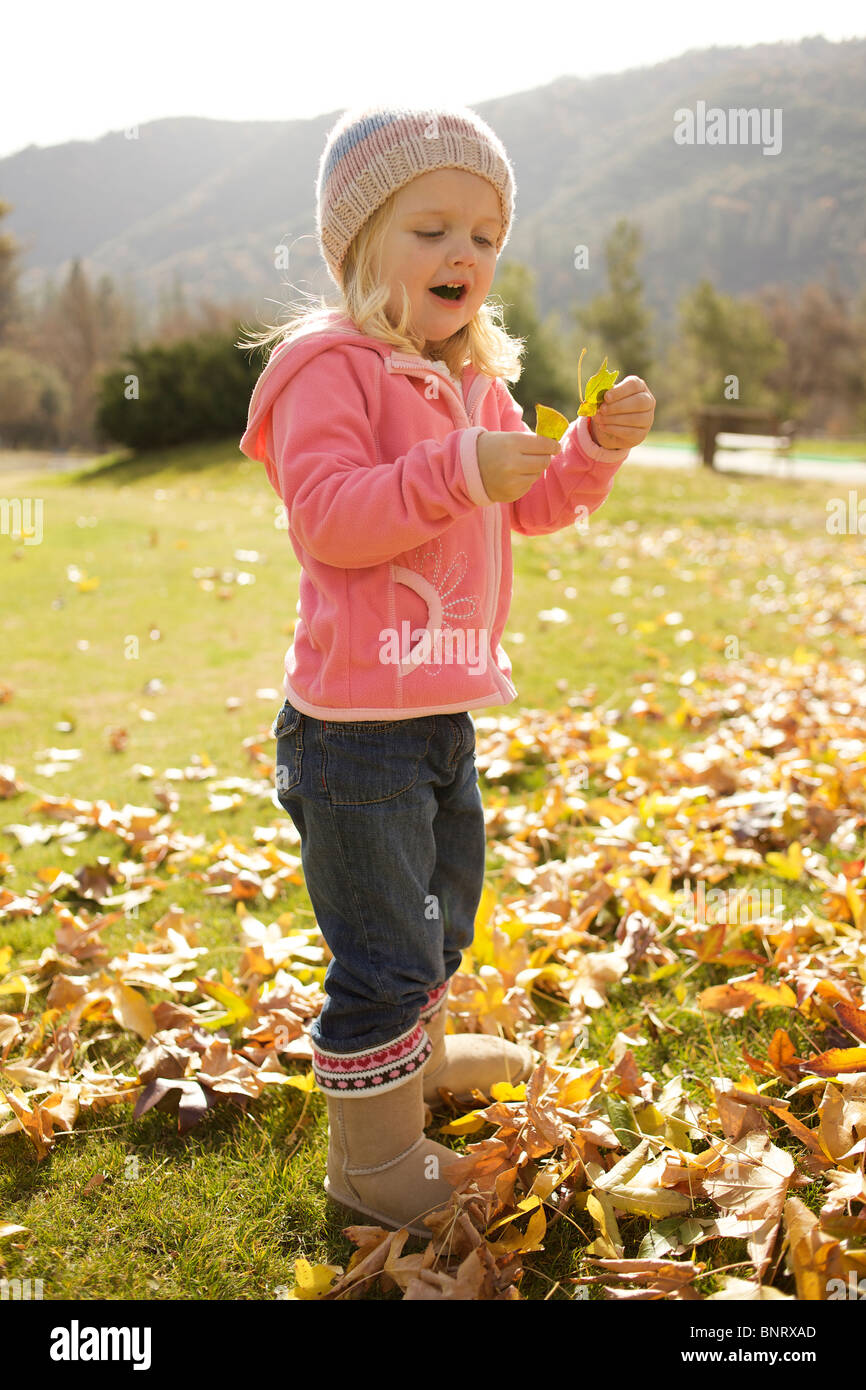 Young girl picks up dry leaves. - Stock Image